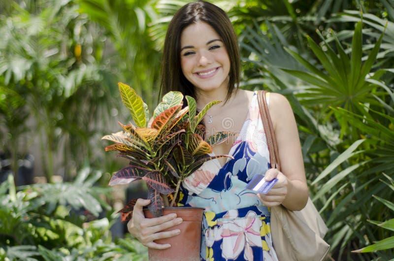 Mujer bonita que compra algunas plantas imagen de archivo