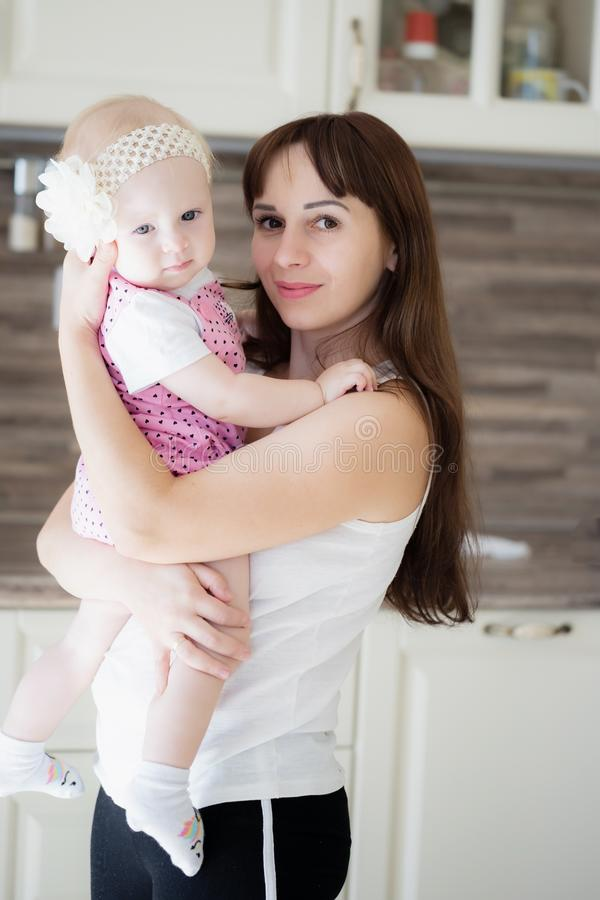 Mujer bonita que detiene a un bebé recién nacido en sus brazos fotografía de archivo