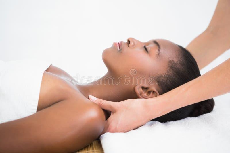 Mujer bonita que disfruta de un masaje del hombro imagenes de archivo