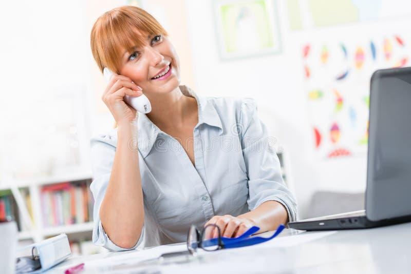 Mujer bonita que habla en el teléfono en la oficina fotografía de archivo