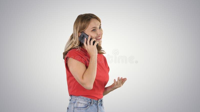 Mujer bonita que habla en el teléfono en fondo de la pendiente fotografía de archivo libre de regalías