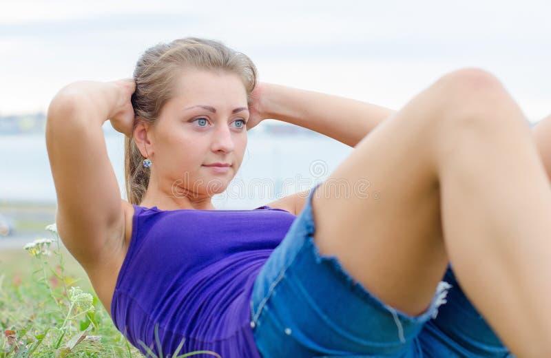 Mujer bonita que hace los ejercicios para el ABS fotografía de archivo