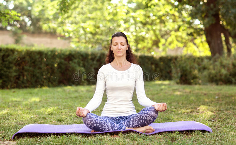 Mujer bonita que hace yoga en parque de la mañana Asana de Lotus Concepto al aire libre de la forma de vida sana Retrato de la na fotos de archivo