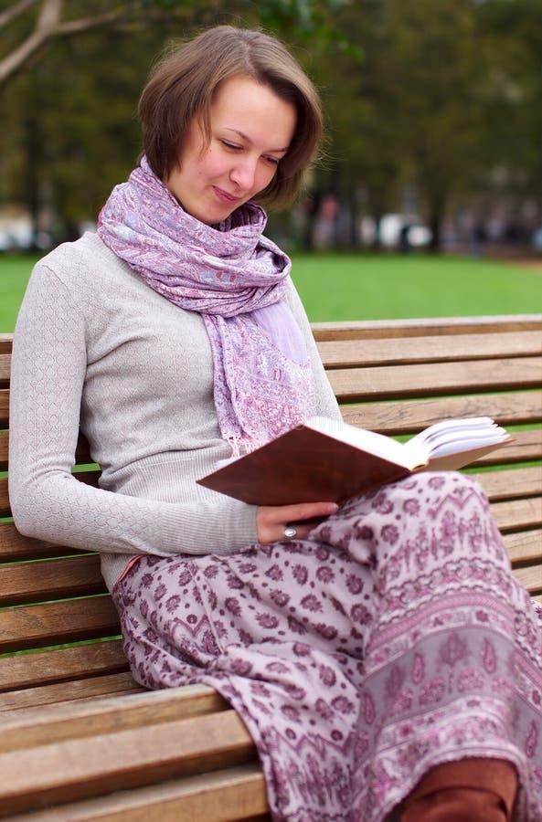 Mujer bonita que lee un libro en un banco y una sonrisa foto de archivo libre de regalías