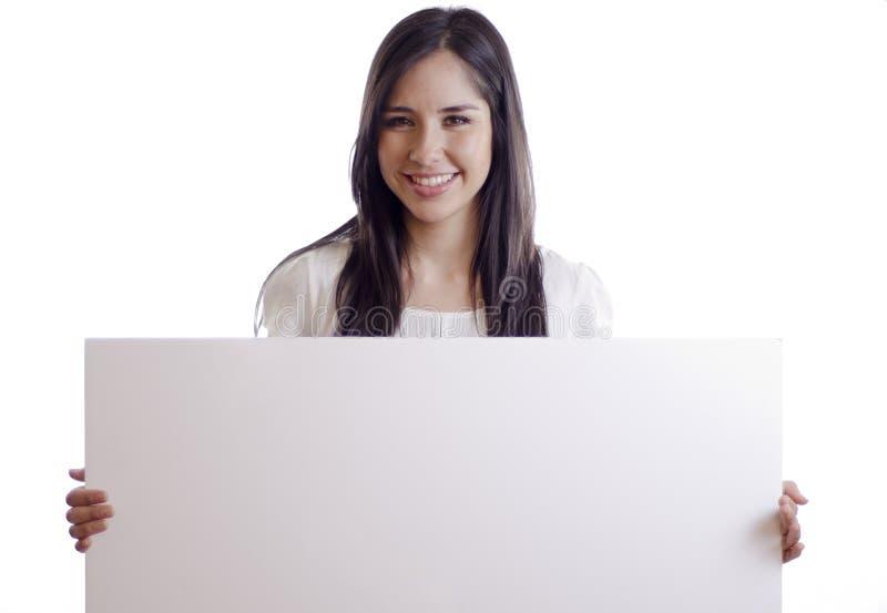 Mujer bonita que lleva a cabo una muestra blanca imagen de archivo
