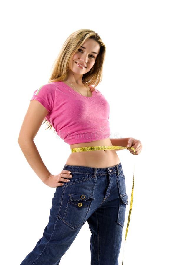 Mujer bonita que mide su pequeña cintura fotos de archivo