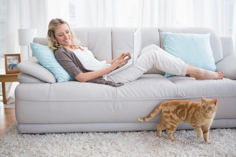 Mujer bonita que miente en el sofá usando su ordenador portátil imágenes de archivo libres de regalías