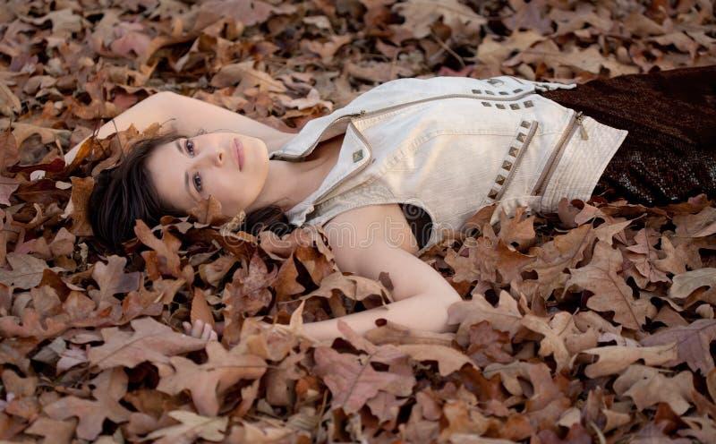 Mujer bonita que miente en las hojas fotografía de archivo