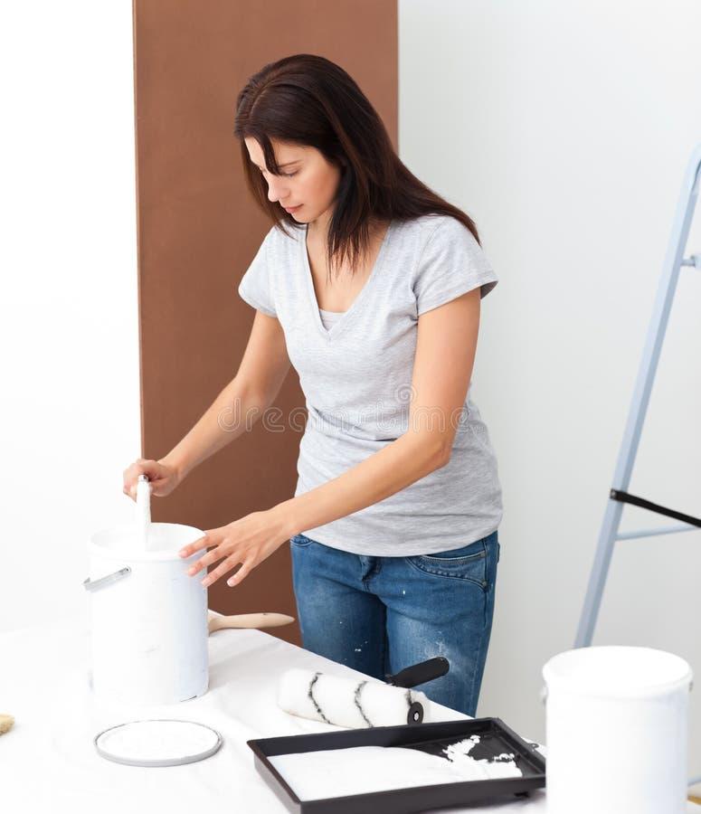 Mujer bonita que prepara la pintura blanca para renovar fotografía de archivo libre de regalías