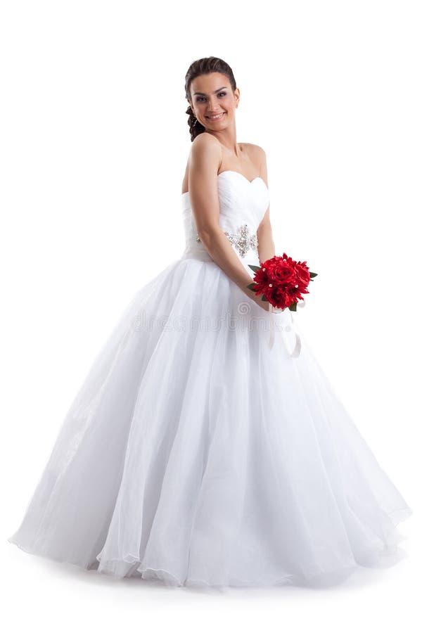 Mujer bonita que presenta en vestido de boda con el ramo imagen de archivo