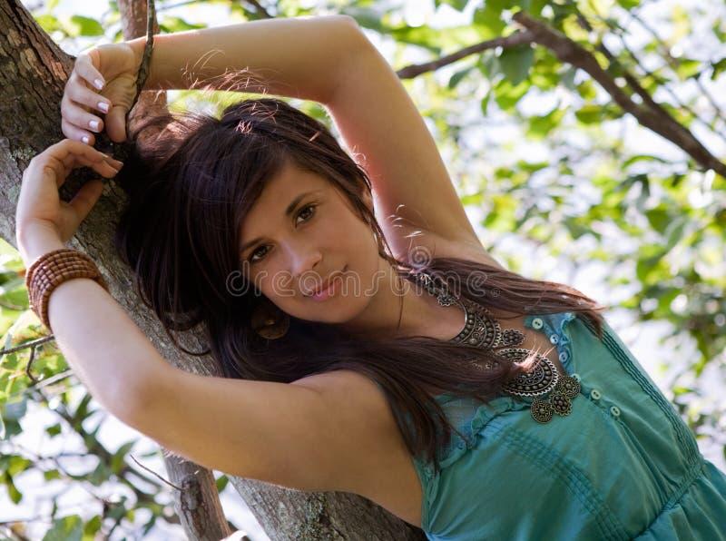 Mujer bonita que se inclina contra árbol fotos de archivo libres de regalías