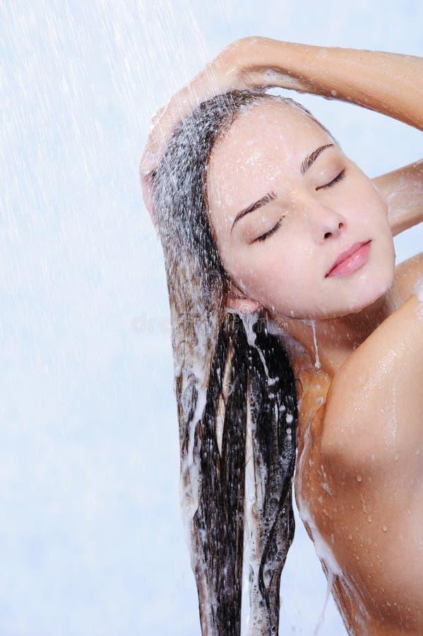 Mujer bonita que se lava el pelo en una ducha fotografía de archivo libre de regalías
