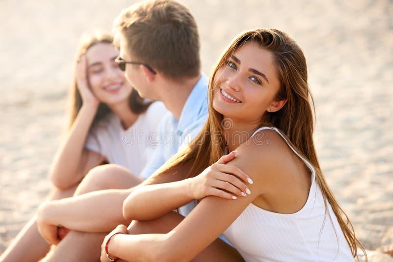 Mujer bonita que se relaja con los amigos que se sientan en la toalla de playa cerca del mar y de tomar el sol Sonrisa bronceada  foto de archivo