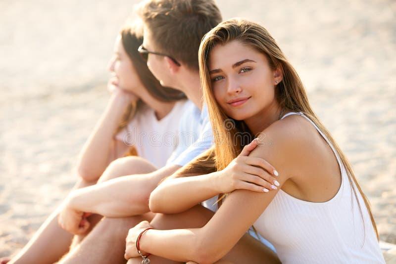 Mujer bonita que se relaja con los amigos que se sientan en la toalla de playa cerca del mar y de tomar el sol Sonrisa bronceada  imagen de archivo