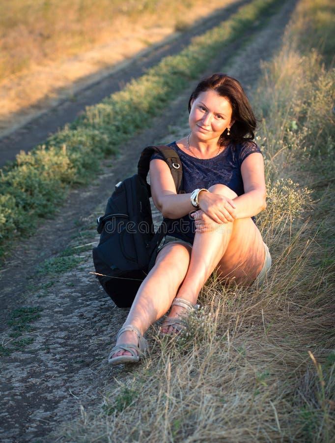 Mujer bonita que se sienta en un camino imagenes de archivo