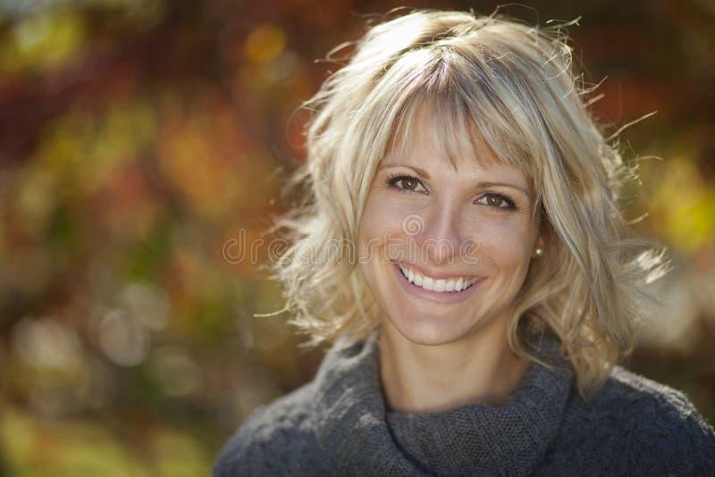 Mujer bonita que sonríe en un bosque imágenes de archivo libres de regalías