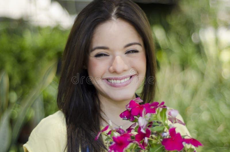 Mujer bonita que sonríe en un jardín fotografía de archivo