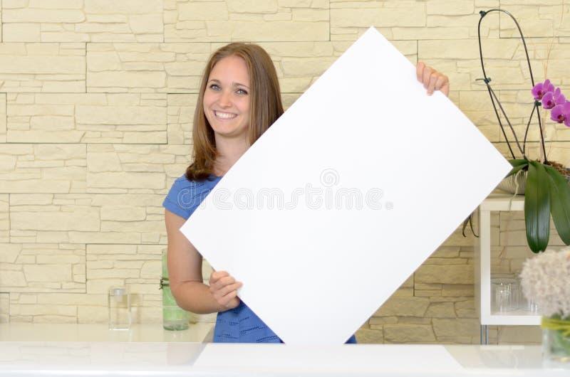 Mujer bonita que soporta una muestra blanca en blanco fotos de archivo libres de regalías