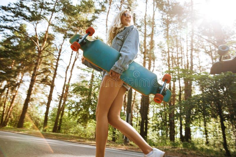 Mujer bonita que sostiene el monopatín al aire libre Mirada a un lado imágenes de archivo libres de regalías