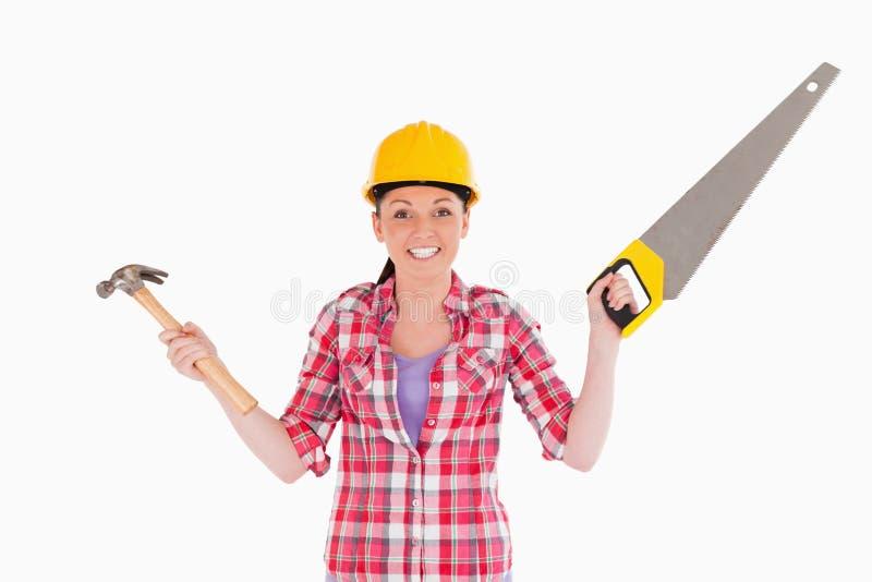 Mujer bonita que sostiene una sierra y un martillo fotos de archivo libres de regalías