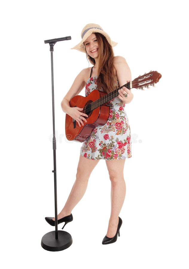 Mujer bonita que toca la guitarra y que canta fotografía de archivo
