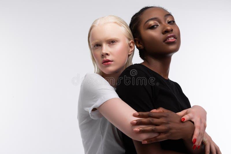 mujer bonita Rubio-cabelluda que abraza a su amigo afroamericano imagenes de archivo