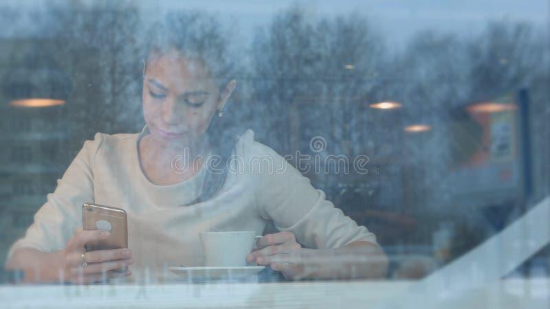 Mujer bonita sonriente con una taza de té que manda un SMS en smartphone en un café fotos de archivo