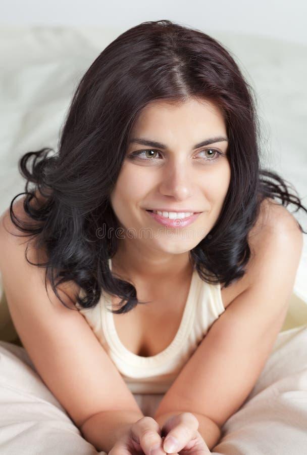 Mujer bonita sonriente en cama fotografía de archivo