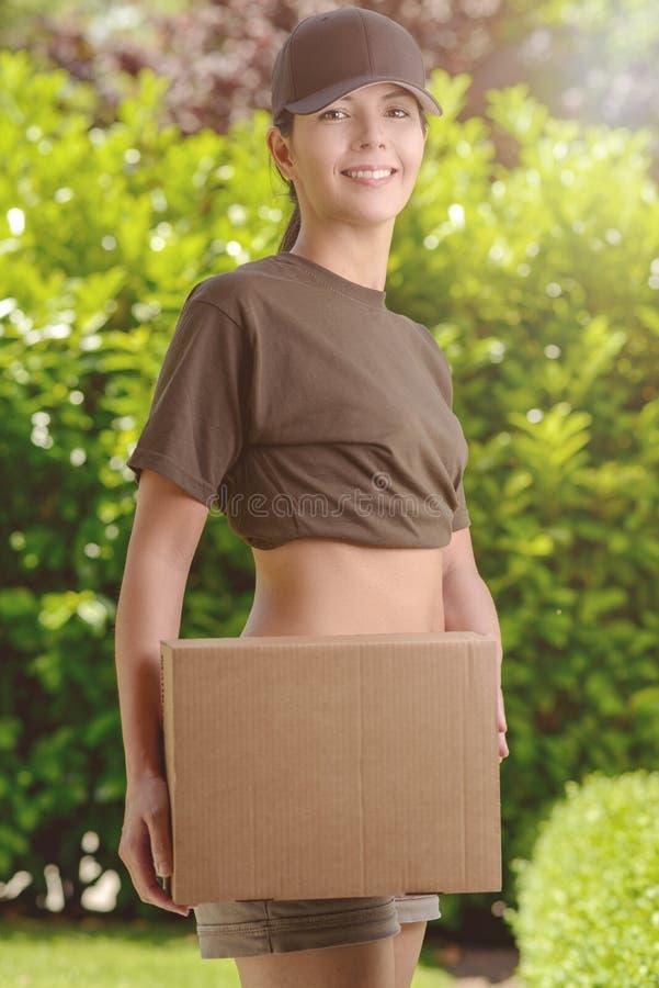 Mujer bonita sonriente en el jardín que sostiene una caja imagen de archivo libre de regalías