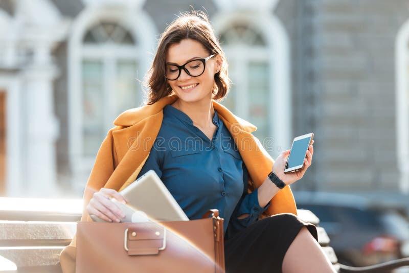 Mujer bonita sonriente en las lentes y la capa que sostienen el teléfono móvil fotografía de archivo libre de regalías