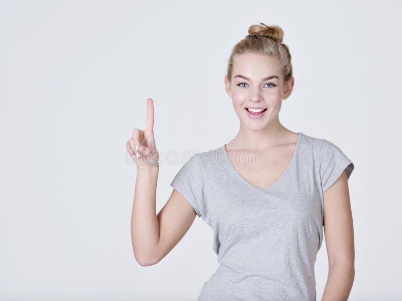 Mujer bonita sonriente que destaca el finger imagen de archivo libre de regalías