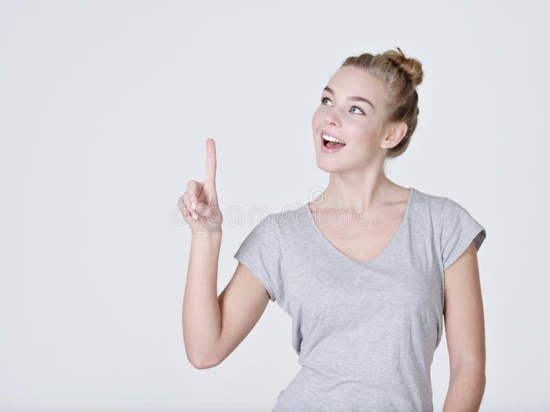 Mujer bonita sonriente que destaca el finger imagen de archivo