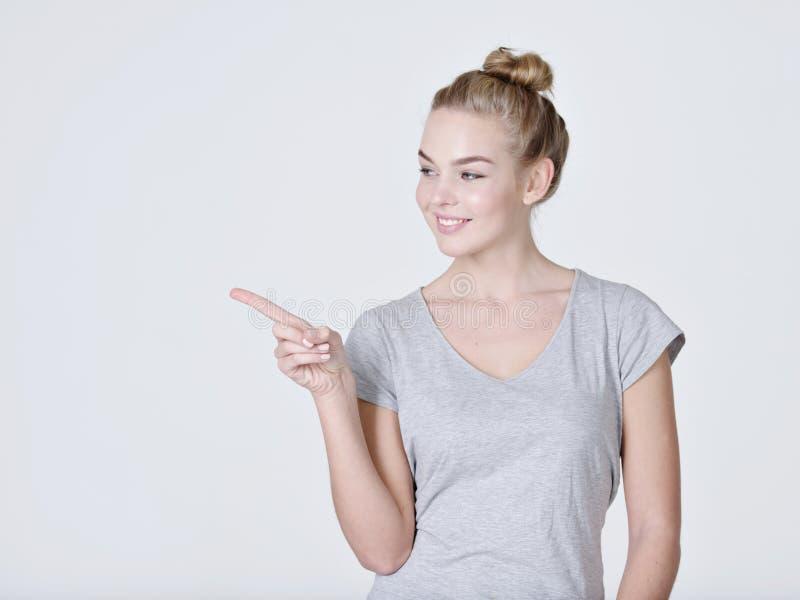 Mujer bonita sonriente que señala el finger lejos fotos de archivo libres de regalías