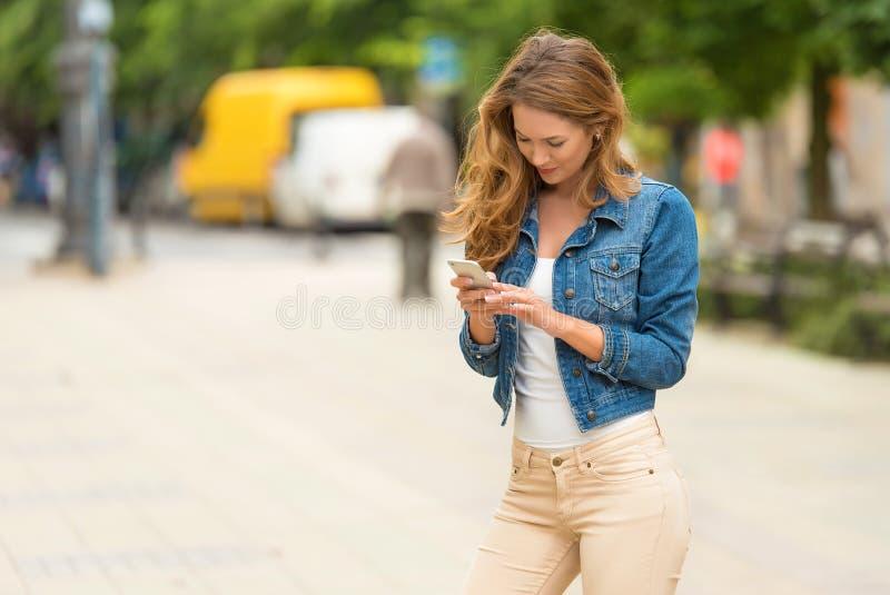 Mujer bonita su teléfono fotografía de archivo