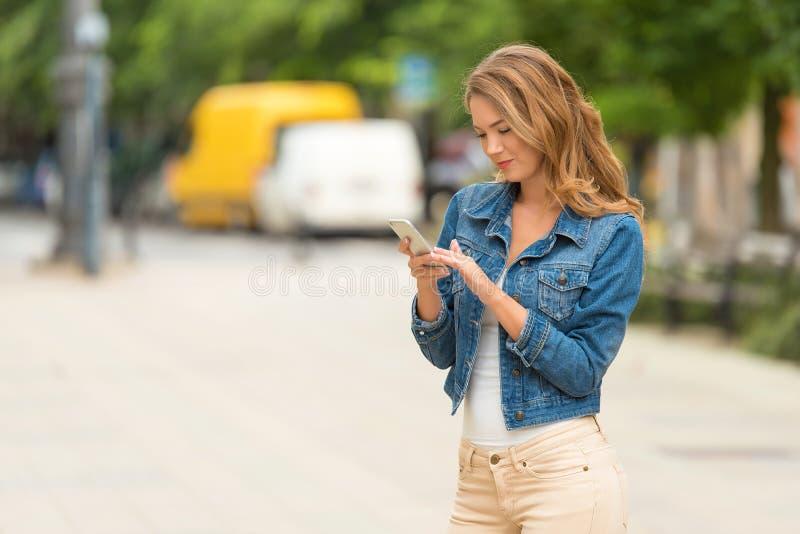 Mujer bonita su teléfono imagenes de archivo