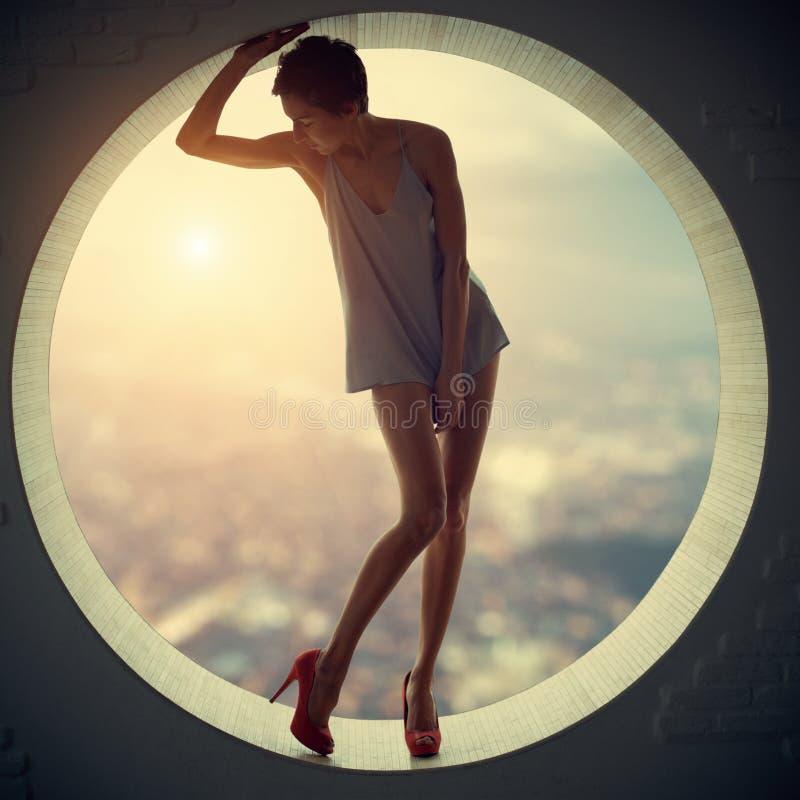Mujer bonita y atractiva delgada adulta joven hermosa de la sensualidad en vestido de moda de la elegancia en una ventana redonda fotografía de archivo