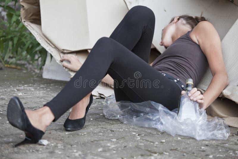 Mujer borracha que duerme en cartones fotos de archivo