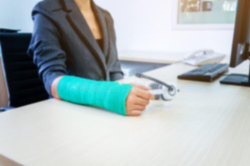 mujer borrosa con la mano quebrada y el molde verde que trabajan en comput fotografía de archivo
