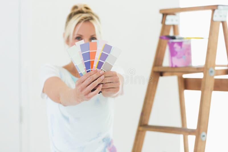 Mujer borrosa que sostiene muestras del color en una nueva casa foto de archivo