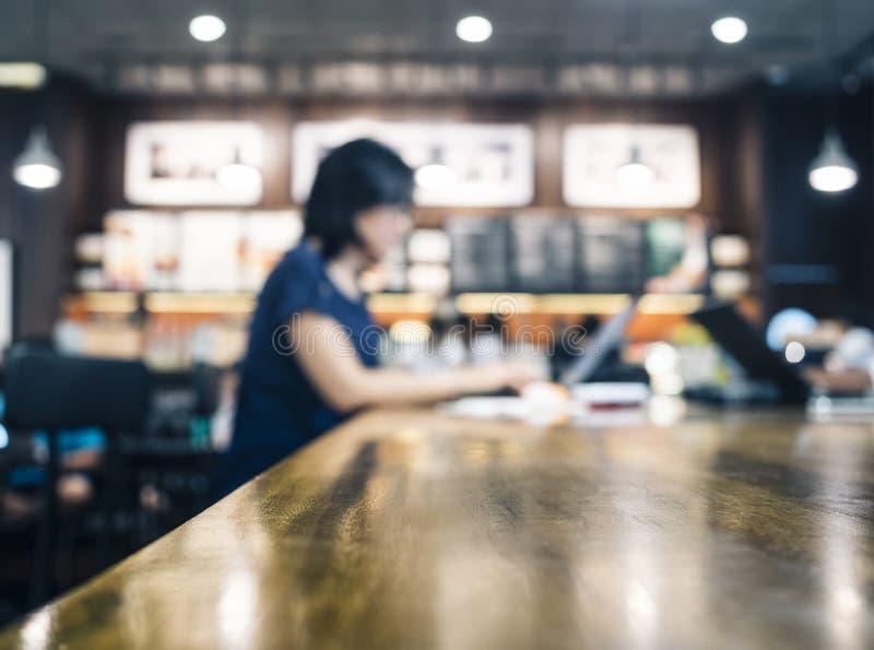 Mujer borrosa que trabaja con el ordenador portátil en la tabla en café fotos de archivo
