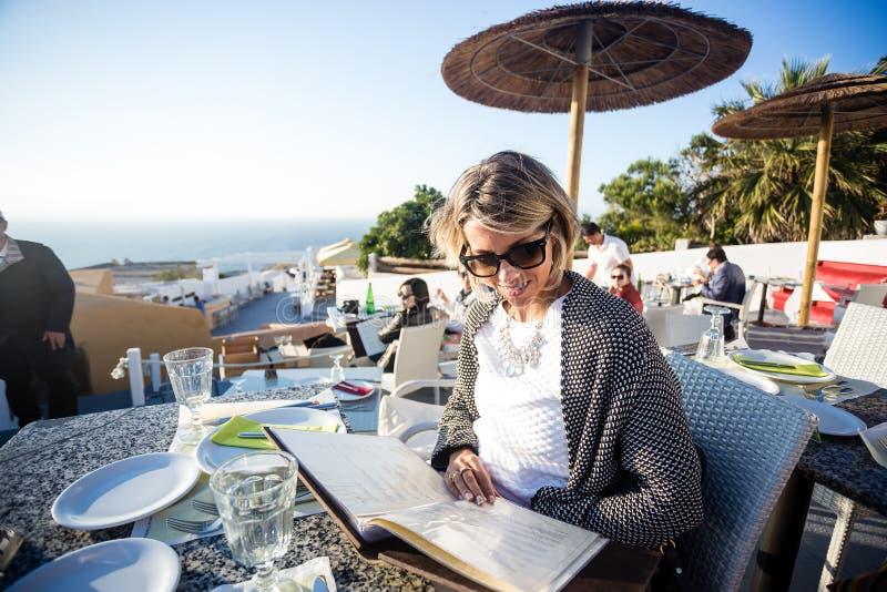 Mujer brasileña rubia atractiva con las gafas de sol que miran el menú en un día de primavera hermoso en Mykonos fotos de archivo