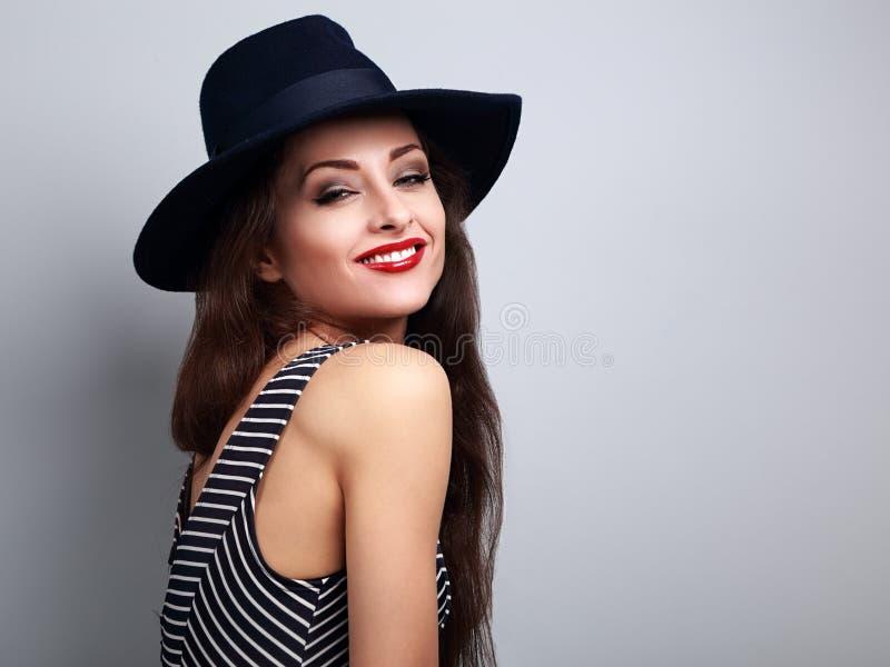 Mujer brillante feliz del maquillaje en sombrero negro de la moda y posi rojo de los labios foto de archivo
