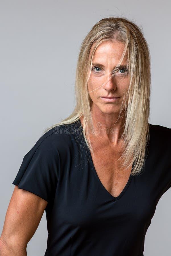 Mujer bronceada atractiva con el pelo rubio largo imagenes de archivo