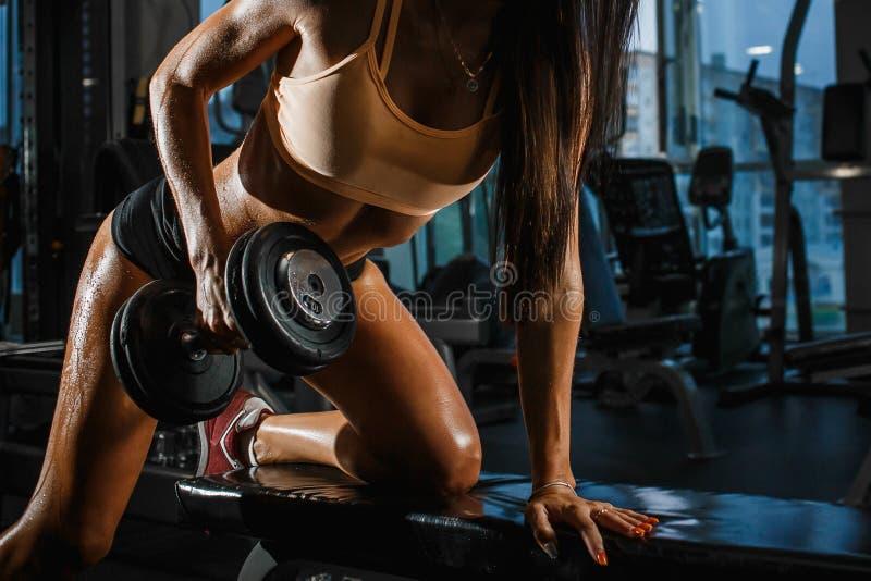 Mujer bronceada deportiva con pesas de gimnasia de elevación de la forma perfecta en el gimnasio Cierre para arriba foto de archivo