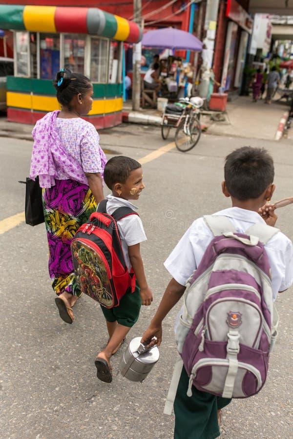 Mujer burmese no identificada que lleva a sus niños a la escuela fotos de archivo