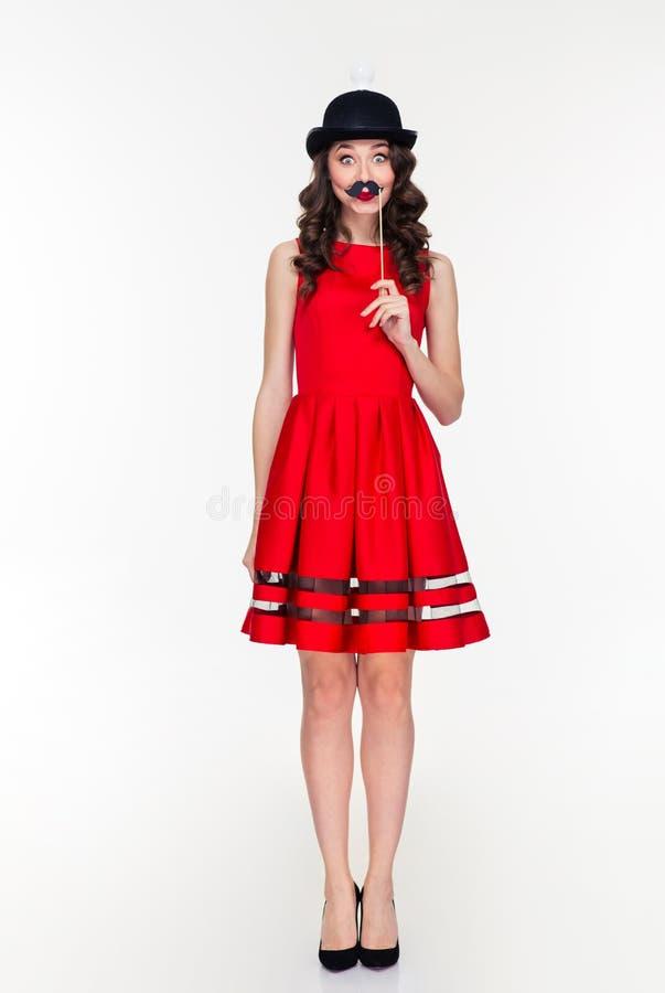 Mujer cómica en sombrero con la bombilla que sostiene el bigote falso imagenes de archivo
