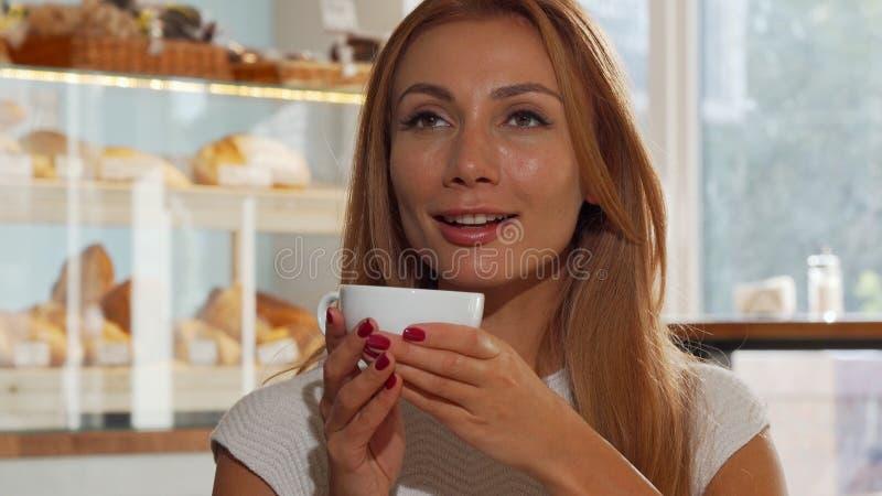 Mujer cabelluda del jengibre feliz que sonríe alegre, café delicioso de consumición imágenes de archivo libres de regalías