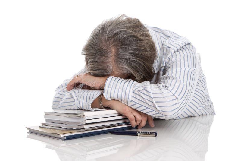 Mujer cabelluda gris que duerme en los libros - con exceso de trabajo aislada en whi imagen de archivo libre de regalías