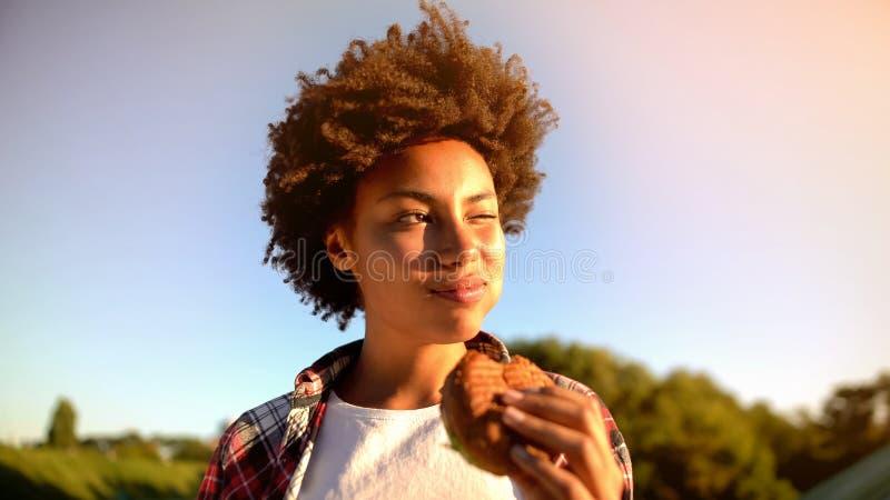 Mujer cabelluda rizada linda que goza de aire libre sabroso de la hamburguesa, del bocado gordo y de los alimentos de preparaci?n fotografía de archivo libre de regalías
