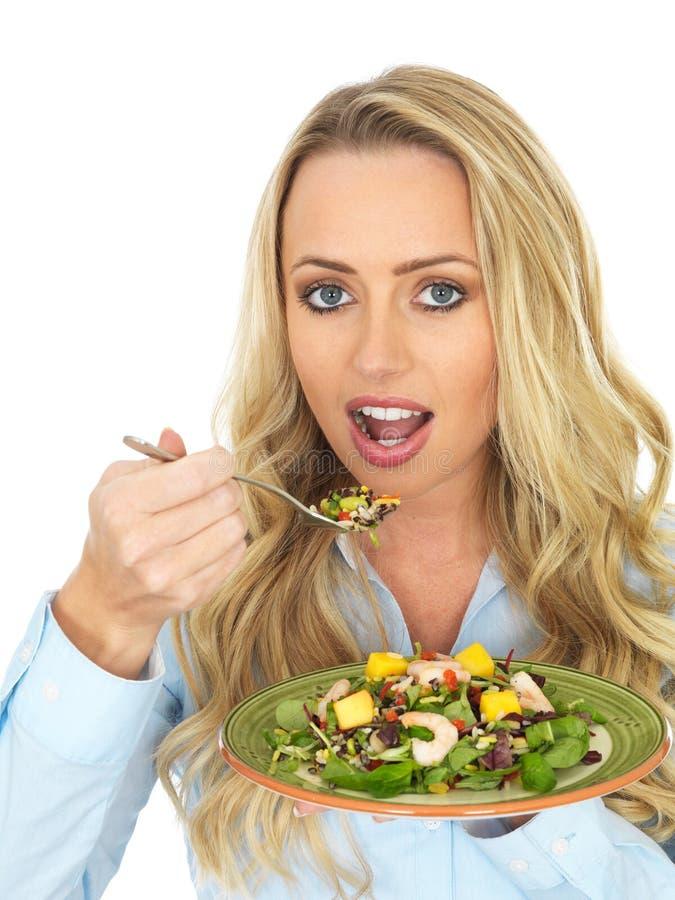 Mujer cabelluda rubia joven atractiva que come una ensalada fresca y sana de la gamba fotografía de archivo